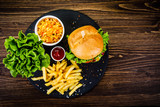 Tasty burger with chips served on stone plate  - 217519039