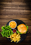 Tasty burger with chips served on stone plate  - 217519085