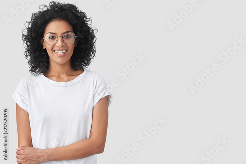 Foto Murales Waist up portrait of happy dark skinned female with Afro hairstyle, smiles gently, being glad to recieve good news, wears casaul white t shirt, stands against studio wall, copy space for advertisement