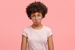 Waist up portrait of dissatisfied African American female with negative angry facial expression, looks in displeasure at someone, wears casual t shirt, being annoyed spend weekend at home alone