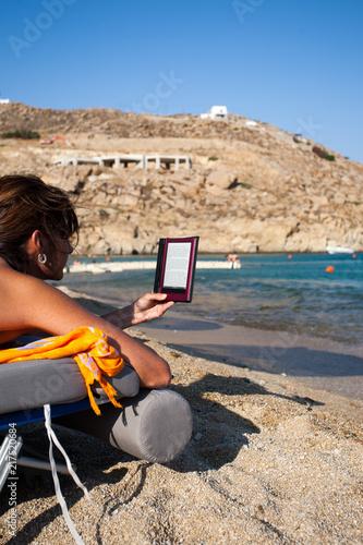 Donna legge libro digitale in spiaggia