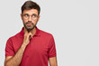 Leinwanddruck Bild - Pensive dreamy male with European appearance looks thoughtfully upwards, thinks about something, analyzes life situation, wears red t shirt, stands against white background with free blank space