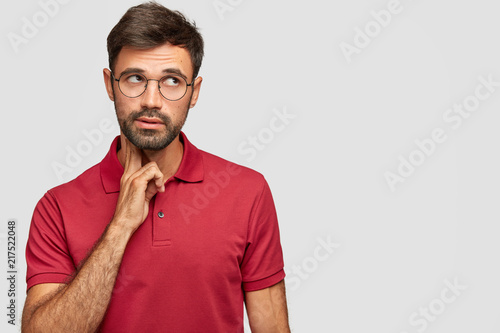 Leinwanddruck Bild Pensive dreamy male with European appearance looks thoughtfully upwards, thinks about something, analyzes life situation, wears red t shirt, stands against white background with free blank space
