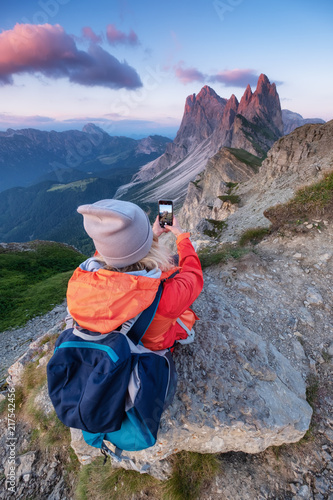 Foto Murales Tourist make a photo by a phone on the high mountain top. Adventure and travel concept. People traveling in the mountains. Dolomite Alps, Italy.