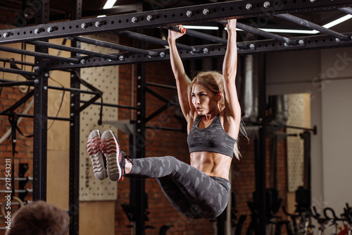 Plexiglas Fitness close up side viow blonde strong woman is hanging on the horizontal bar. cross fit , health care concept