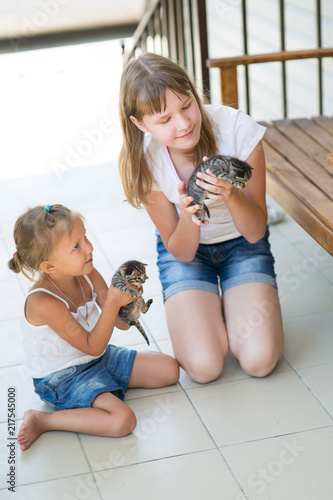 Children play with kittens