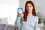 Young redhead girl holding vintage alarm clock on unfocused background - 217545425