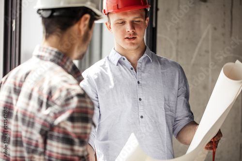 two people having a degree of engineering with blueprint. close up portrait