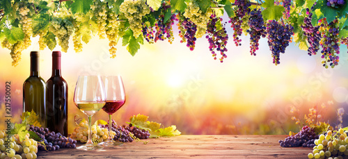 obraz lub plakat Bottles And Wineglasses With Grapes At Sunset