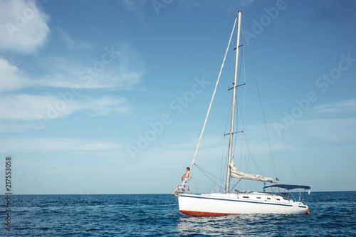 Floating sailing boat with sails down in calm sea. A boat lowered the sails and anchored near the coast
