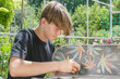 Young guy repairs a skateboard board in the garden on a sunny day