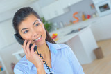Woman at home talking on land line telephone - 217554268