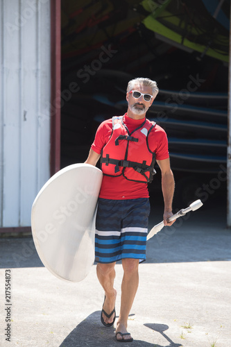 Foto Murales man holding stand up paddle board walking towards the water