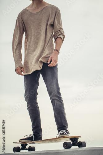 Leinwandbild Motiv man ready to extreme ride wooden longboard skateboard. Good summer day for skateboarding