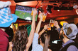 Quadro group or company of friends - young guys and girls holding glasses of beer, watching football, laughing and smiling at the bar during the Oktoberfest festival