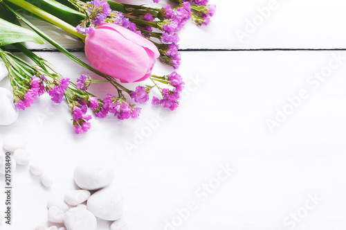 Foto Murales Pink tulips and white pebbles on a white wooden background