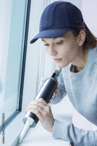 Foto Murales Woman applying silicone to window