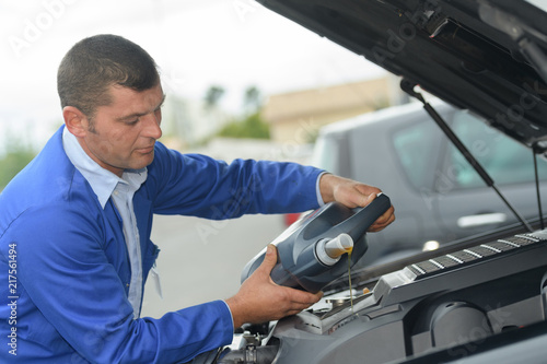 mata magnetyczna mechanic checking oil level in a car workshop