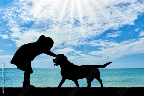 Foto Murales Silhouette of a baby girl stroking a dog against the sea