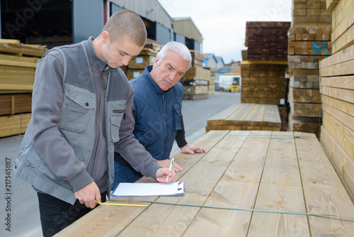 Men with clipboard looking at stack of wood - 217565087