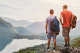 friends hiking in Europe, hike in Alps in Annecy, France, outdoor summer activity with backpack, two people backpackers standing on top of mountain and enjoying beautiful nature landscape background - 217568826