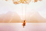 inspiration, travel and daydream concept, beautiful young woman romantic dreamer on the swing in amazing summer inspirational landscape background - 217569487