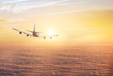 airplane flying above clouds, aircraft traveling in the sky, flight at sunset - 217569499