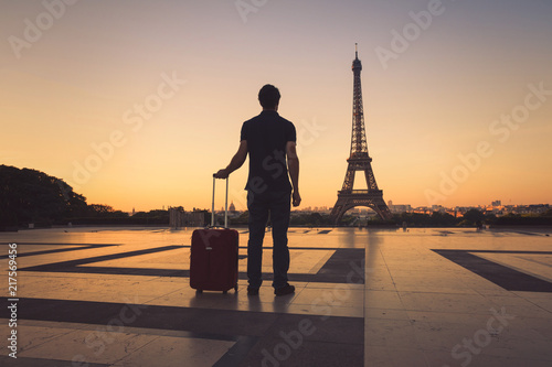 Wall mural tourist in Paris looking at Eiffel Tower, silhouette of man with luggage travel to France