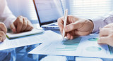 business analytics, team of people working on financial report in the office, teamwork, closeup of hands - 217569639
