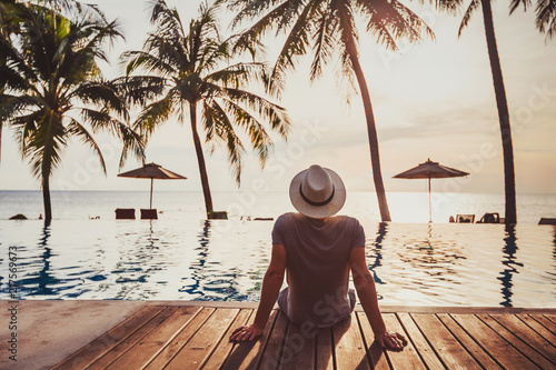 Leinwanddruck Bild tourist in luxury beach hotel near luxurious swimming pool at sunset, tropical exotic holidays vacation, tourism and travel