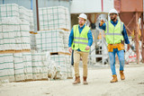 Two young men in hardhats and waistcoats pointing at distance while walking near stacks of building materials during inspection on construction site - 217572032