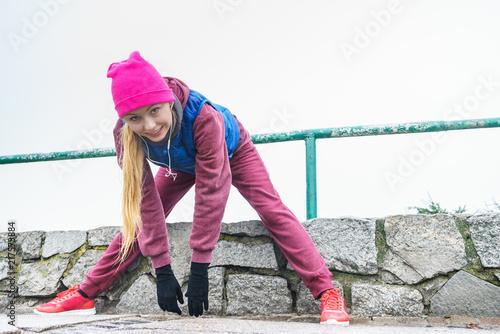 Foto Murales Woman wearing sportswear exercising outside during autumn