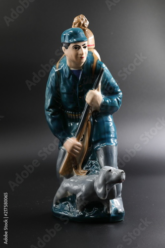 Porcelain figure of the hunter with a dog against a dark background, subject shooting.