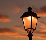 Antike Laterne vor dramatischem Himmel bei Sonnenuntergang - 217582616