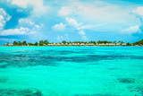 Tropical and exotic seascape with turquoise lagoon water and overwater villas in the background. - 217584859