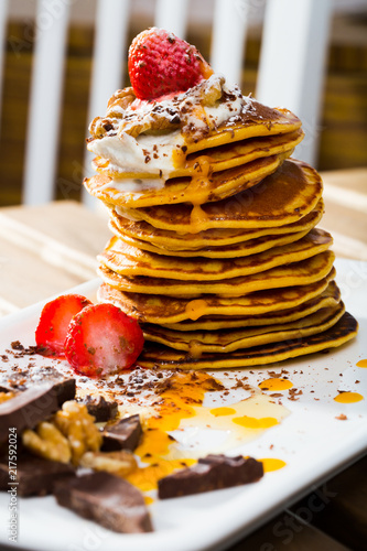 Foto Murales Stack of sweet pancakes with  fruit, honey, chocolate and whipped cream