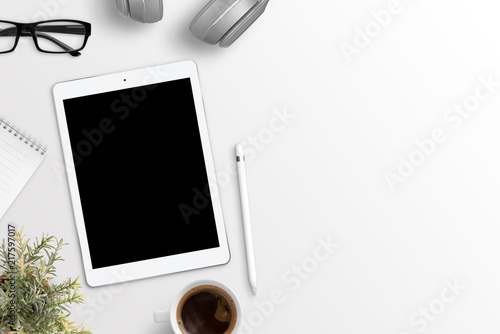 Tablet mockup on white desk with free space on right side for text. Flat lay composition.