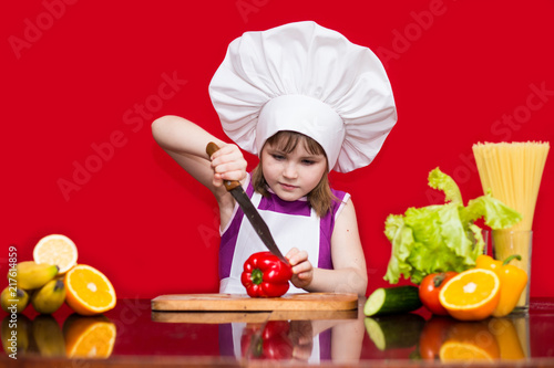 Fridge magnet Happy little girl in chef uniform cuts vegetables in kitchen. Kid chef. Vegetarian. Cooking Process Concept