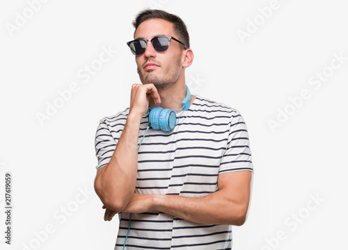 Foto Murales Handsome young man wearing headphones with hand on chin thinking about question, pensive expression. Smiling with thoughtful face. Doubt concept.