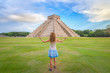 Young woman enjoying the amazing Kukulkan pyramid in Chichen Itza, Mexico