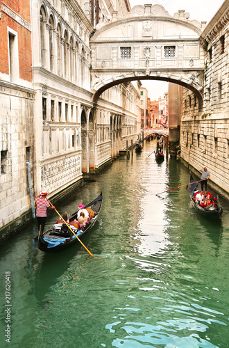 Gondolier carrying tourists in their gondola, by the bridge of sighs in venice, italy at sunset