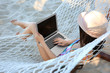 Leinwanddruck Bild - Young woman with laptop resting in hammock at seaside. Summer vacation