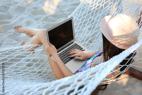 Leinwanddruck Bild Young woman with laptop resting in hammock at seaside. Summer vacation