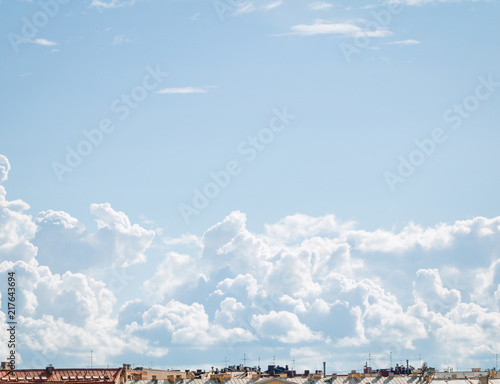 Foto Murales Blue sky witn fluffy white clouds above roofs in city in Europe. Place for text.