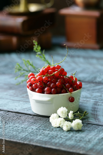 Foto Murales red currant in a cup on a wooden table