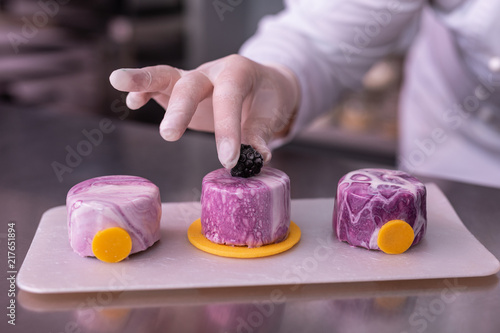 Fridge magnet Confectionary masterpiece. Female chef finishing her perfect confectionary masterpiece while decorating cakes with mulberry