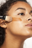portrait of a young dark-skinned woman applying liquid makeup base with brush on her face on a white background - 217655622