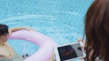 Couple using mobile phone to take photos at the poolside - 217659042