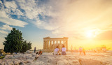 Tourists sitting on stones in front of Parthenon in the evening during sunset time, Athens, Greece. Picturesque sky at the Parthenon temple - 217660012