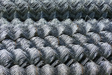 Rolls of galvanized steel wire mesh with a large cell and twisted pattern close-up. In the category of texture, screen saver, wallpaper. - 217660053